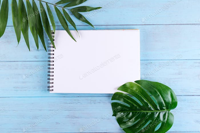 Palm leaves and a paper notebook with free space for text on blue wooden background
