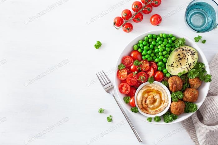 healthy vegan lunch bowl with falafel hummus tomato avocado peas