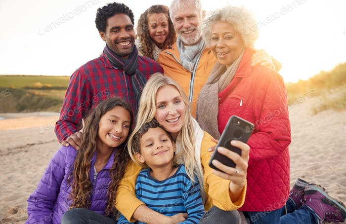 Multi-Generation Family Sitting By Fire On Winter Beach Vacation Taking Selfie