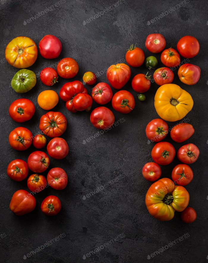 Letter M made with ripe tomatoes on a black background, creative flat lay healthy food concept