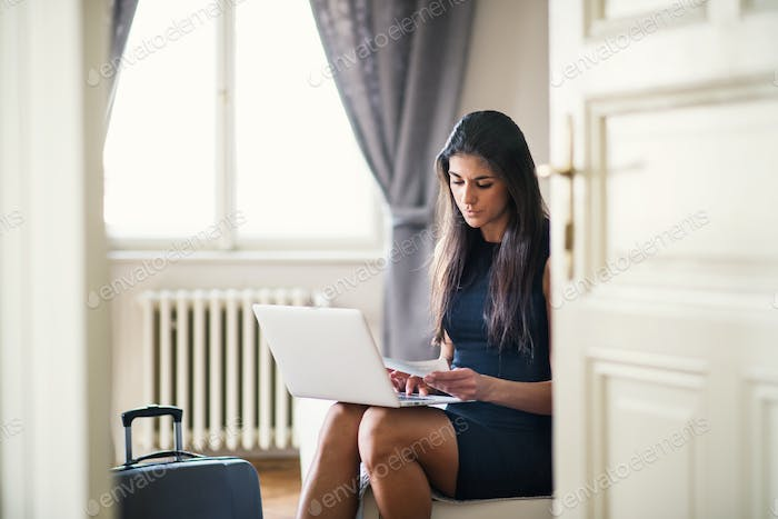 Young businesswoman on a business trip sitting in a hotel room, using laptop.