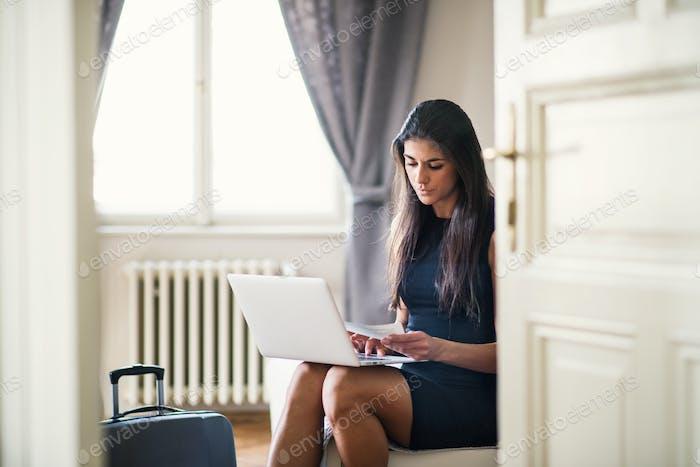 Junge Geschäftsfrau auf einer Geschäftsreise sitzt in einem Hotelzimmer, mit Laptop.