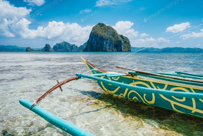 Holiday vacation vibes, tourism vivid colored boat on tropical sandy beach with island, blue sky and