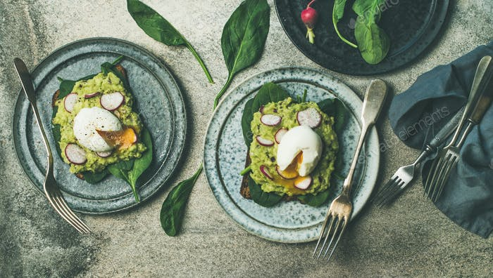 Healthy vegetarian breakfast flat-lay. Avocado and egg toasts, wide composition