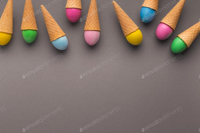 Colorful easter eggs in waffle cones on gray background