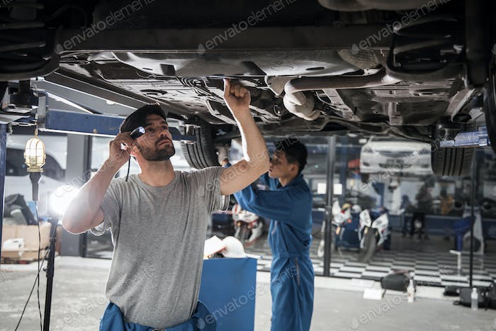 Two mechanic was checking the car suspension.