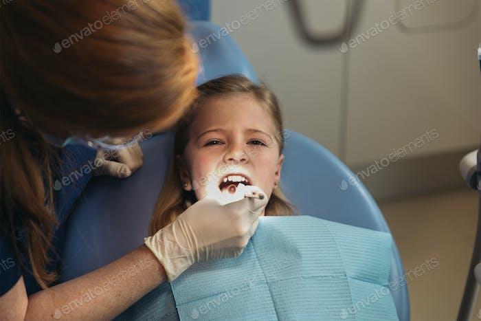 Dentistas con un paciente durante una intervención dental a la niña.