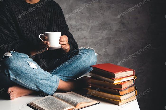 Mädchen liest Bücher, studieren, entwickeln mit einer Tasse Kaffee auf einem weißen Tisch und einem grauen Hintergrund