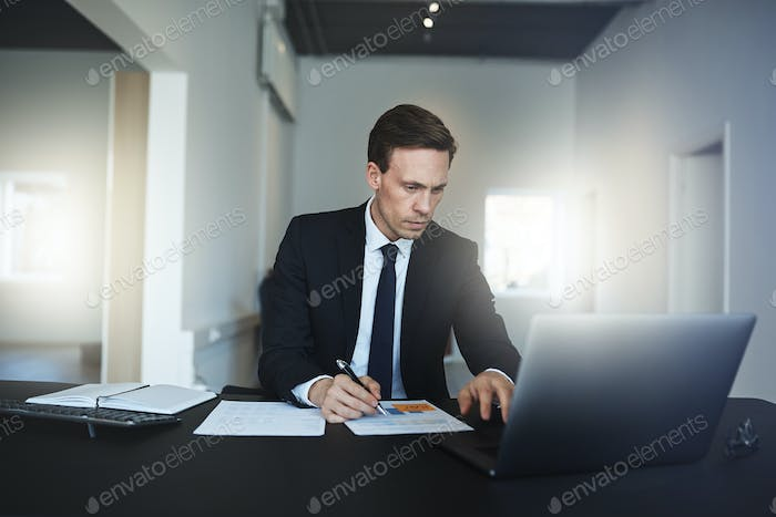 Businessman reading paperwork and using a laptop in an office