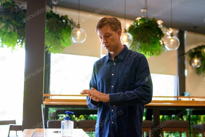 Junge gut aussehende Geschäftsmann mit Hand Desinfektionsmittel als richtige Hygiene Etikette im Café