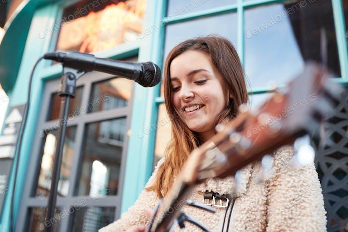 weiblich musiker busking spielen akustische gitarre und singen im freien in street