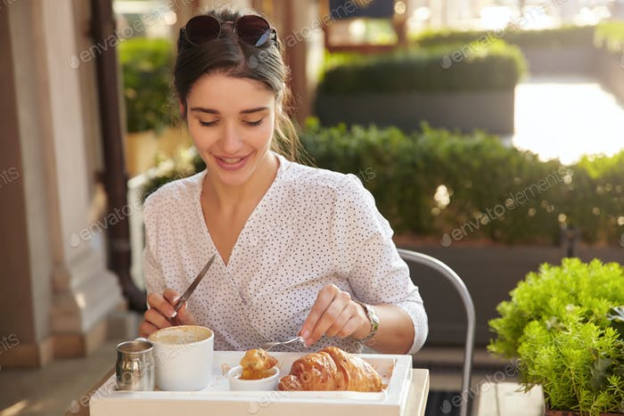 Sunny photo of young positive lovely brunette lady with sunglasses having fresh croissant