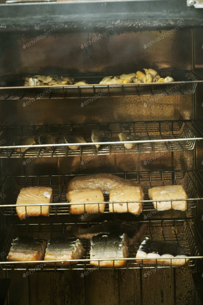 Fish fillets on racks in a fish smoker.