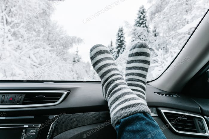 Woman feet in warm socks on car dashboard. Winter time, travel concept.