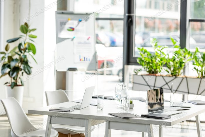 office with table, chairs, green plants and digital devices