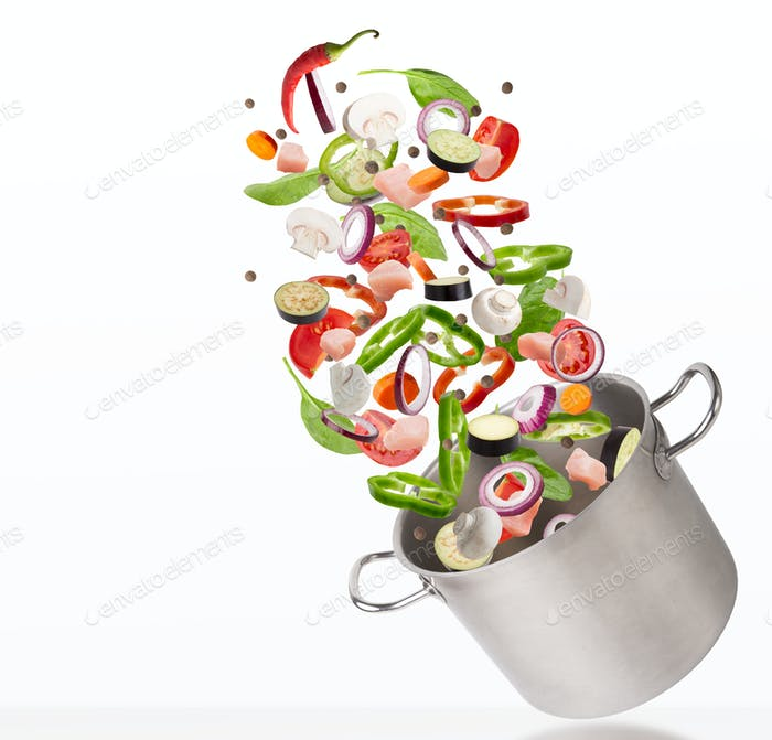 Fresh vegetables and raw meat flying into steel stewpot