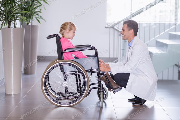 Smiling doctor talking to disable girl