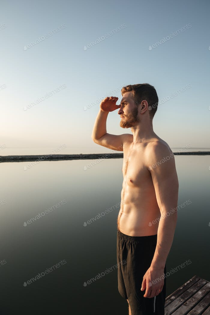 Sports man standing at the beach and looking far away