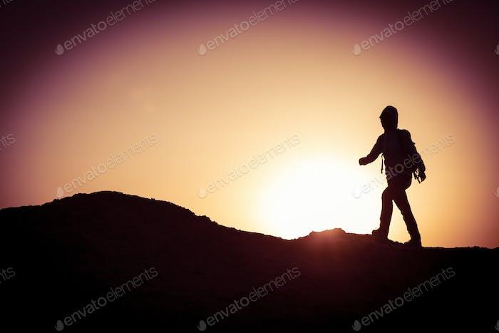 Backpacker hking on sunset desert