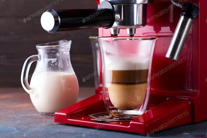 Kaffeemaschine mit frischem Latte Kaffee und Gießen in Glas im Restaurant, Nahaufnahme