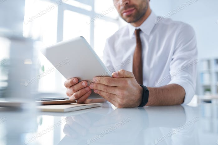 Contemporary director of company using digital tablet