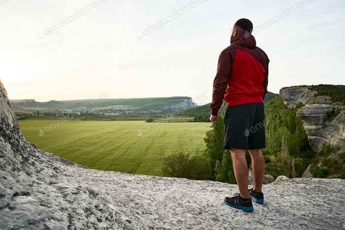 Sporty man standing on hill in the countryside