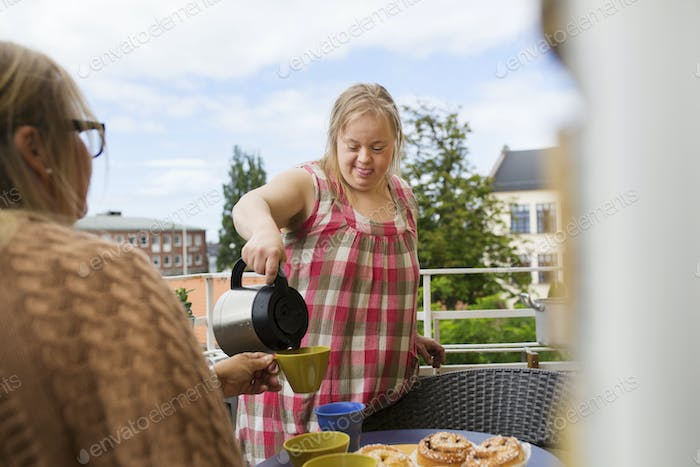 Daughter with down syndrome pouring coffee for mother on balcony