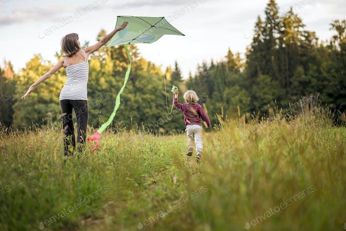 Junge Mutter hilft ihrem Kind, einen Drachen zu fliegen