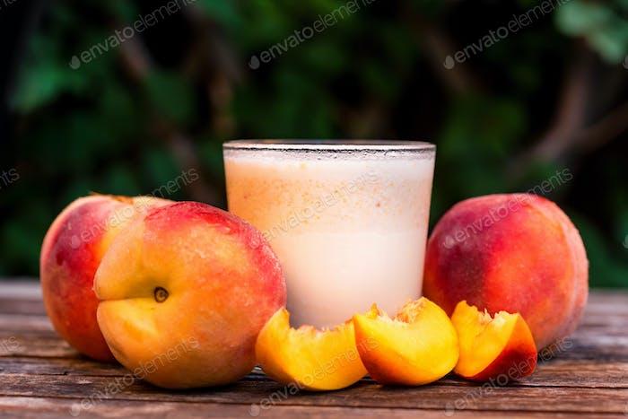 Glas Pfirsichjoghurt und Pfirsiche auf Holztisch