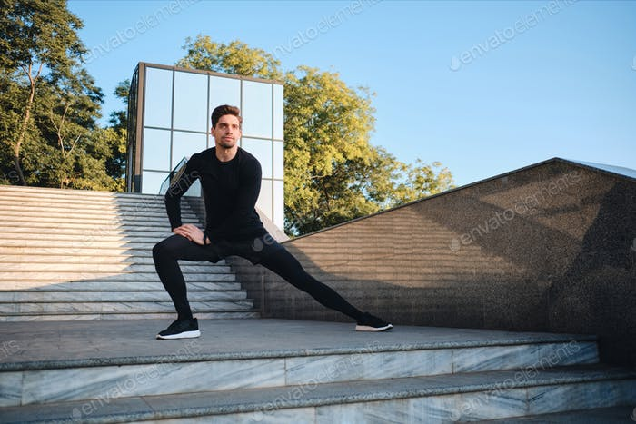 Young attractive sporty man stretching during workout in city park