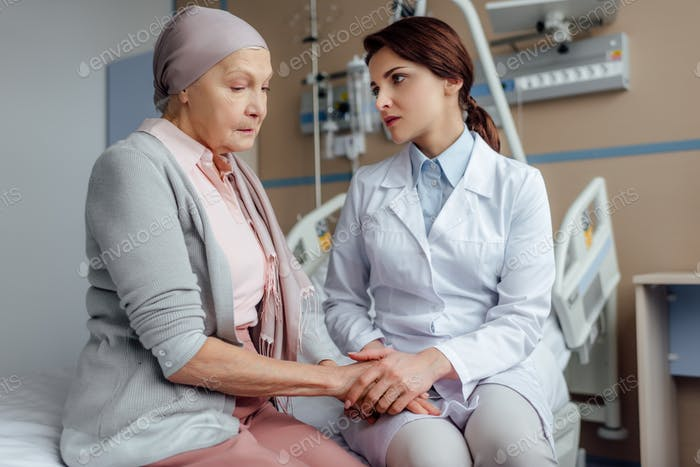 worried female doctor holding hands with senior woman in kerchief with cancer in hospital