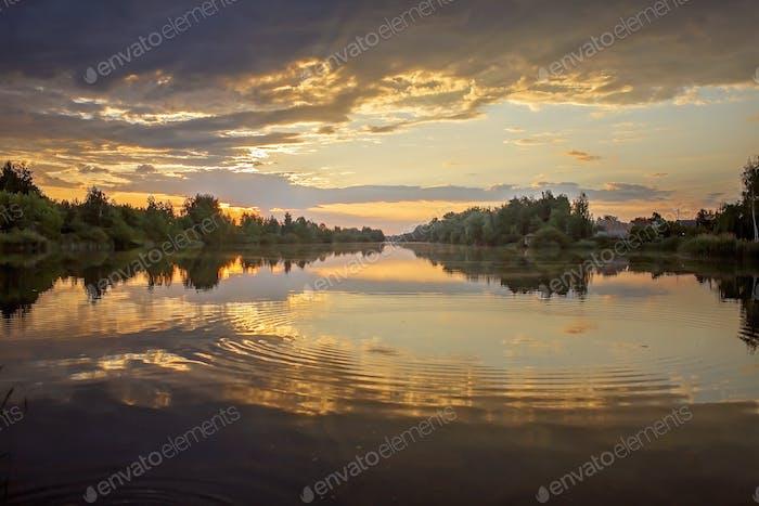 Preciosa puesta de sol sobre el lago, agua como espejo, horas doradas, crepúsculo, viajes locales y naturaleza