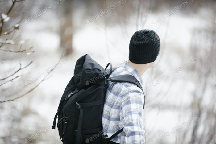 A hiker in the mountains with a rucksack and a woolly hat.