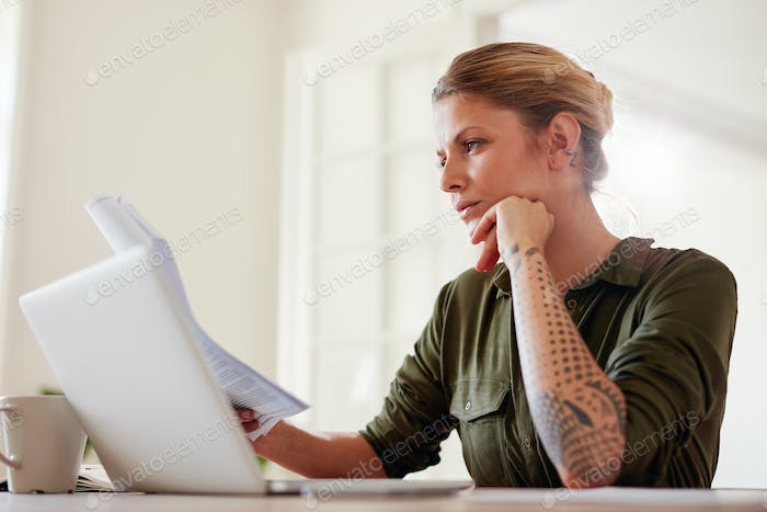 Young woman reading documents at home