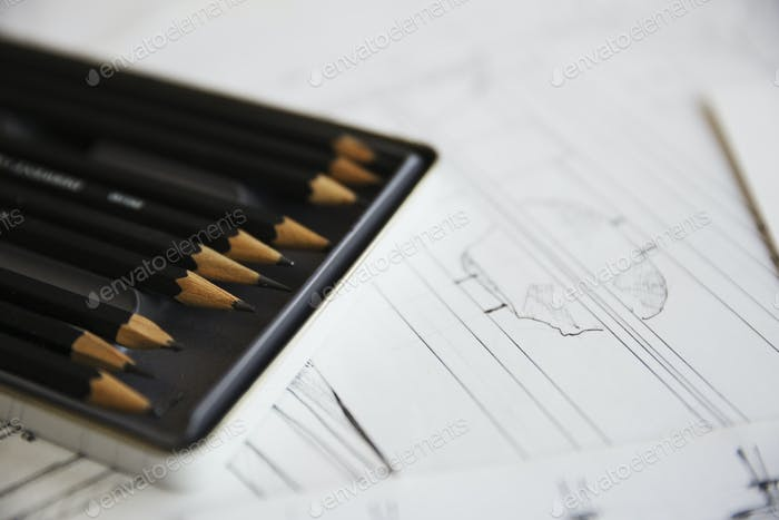 Close up of design drawings for furniture and a tray of pencils.