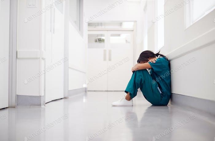 Gestresste und überarbeitete weibliche Arzt tragen Peelings sitzen auf Boden im Krankenhaus Korridor