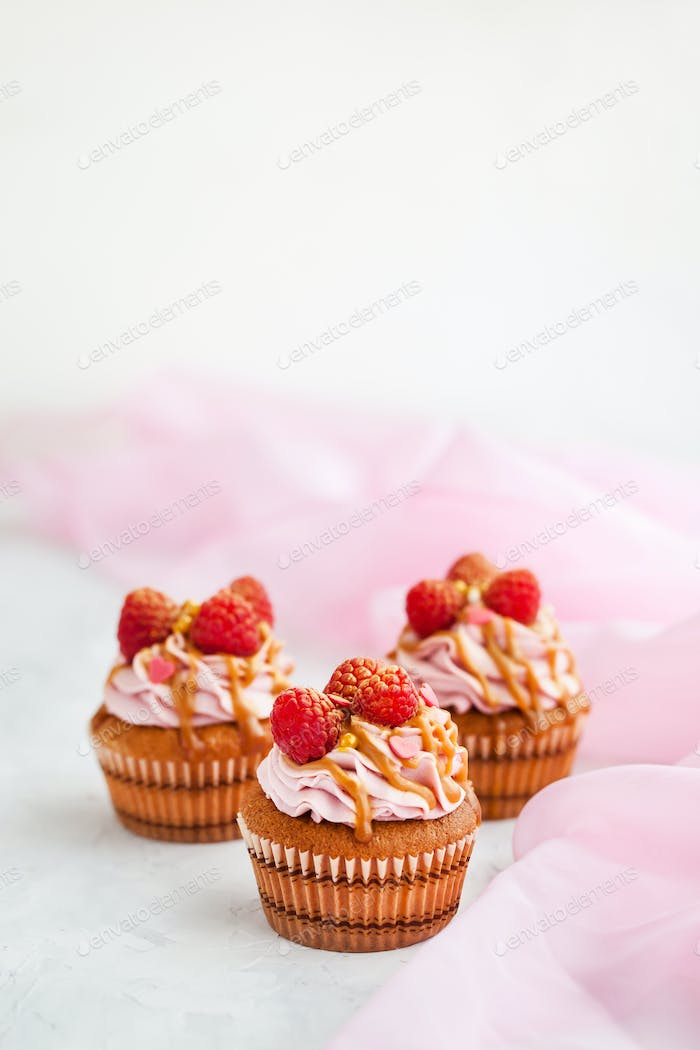 Raspberry and caramel cupcakes on white background