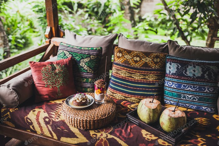 Breakfast outside on sofa with colorful pillows with traditional east ornaments. Pancakes