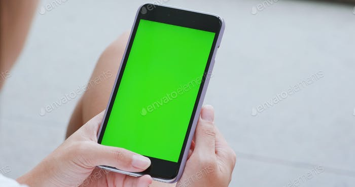 Woman use of smart phone with green screen, chroma key