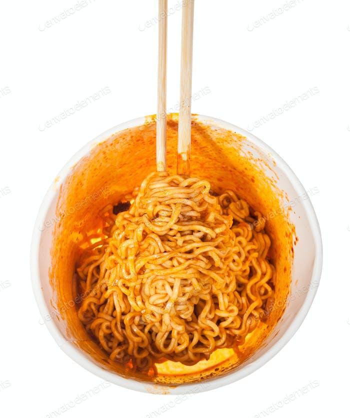 chopsticks in prepared spicy instant noodles
