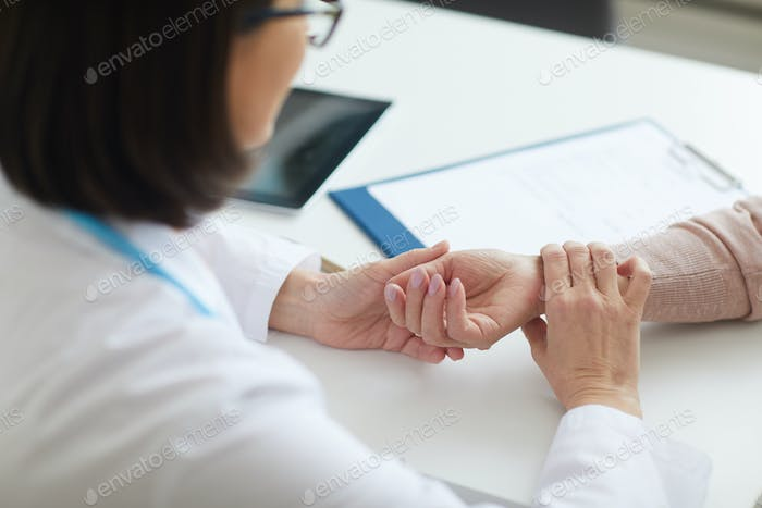 Doctor Checking Pulse of Senior Patient