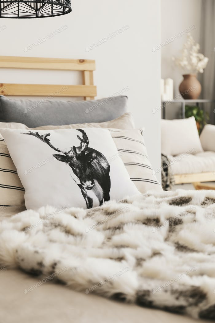 Real photo with close-up of bed with reindeer cushion, many pill