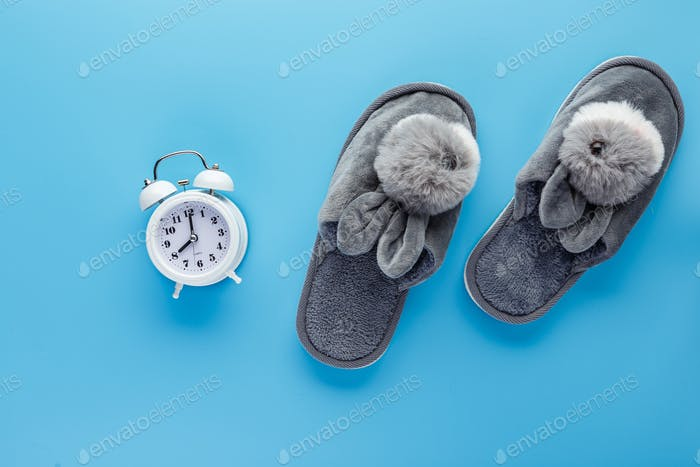 White alarm clock and slippers