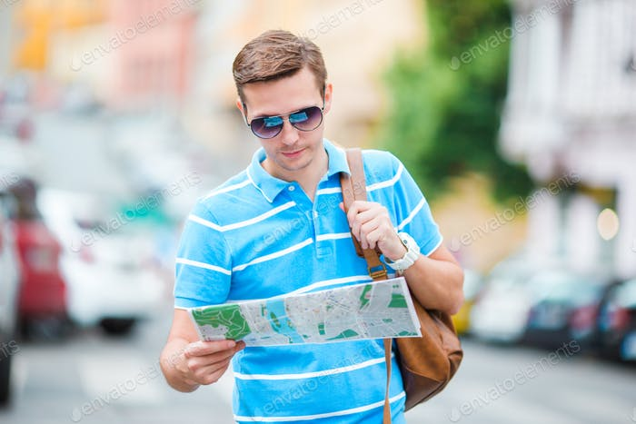 Young caucasian tourist with a city map and backpack in Europe. Happy guy looking at the map of