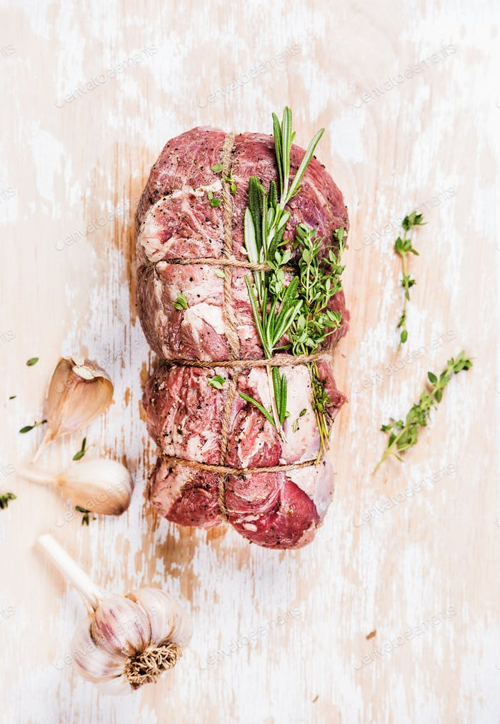 Raw uncooked roastbeef meat cut with rosemary, thyme and garlic