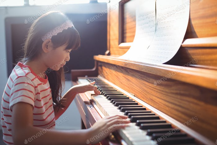 Side view of girl practicing piano in classroom