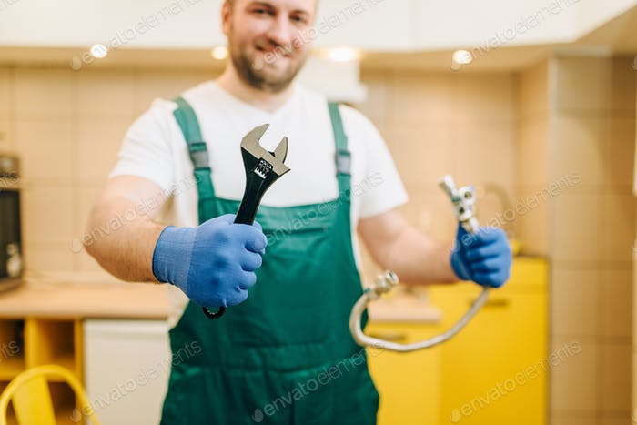 Plumber in uniform holds wrench, handyman