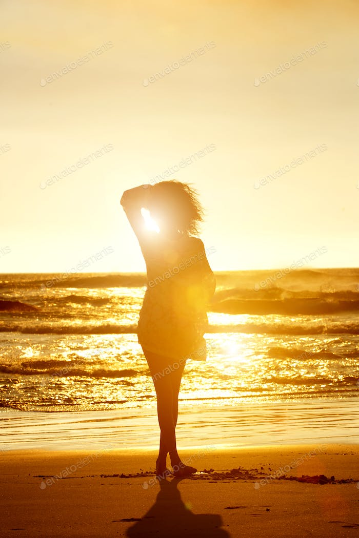 Silhouette of fashion model walking on beach during sunset
