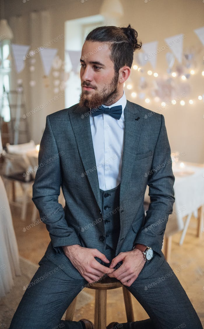 A handsome hipster young man with formal suit sitting on a stool on an indoor party.