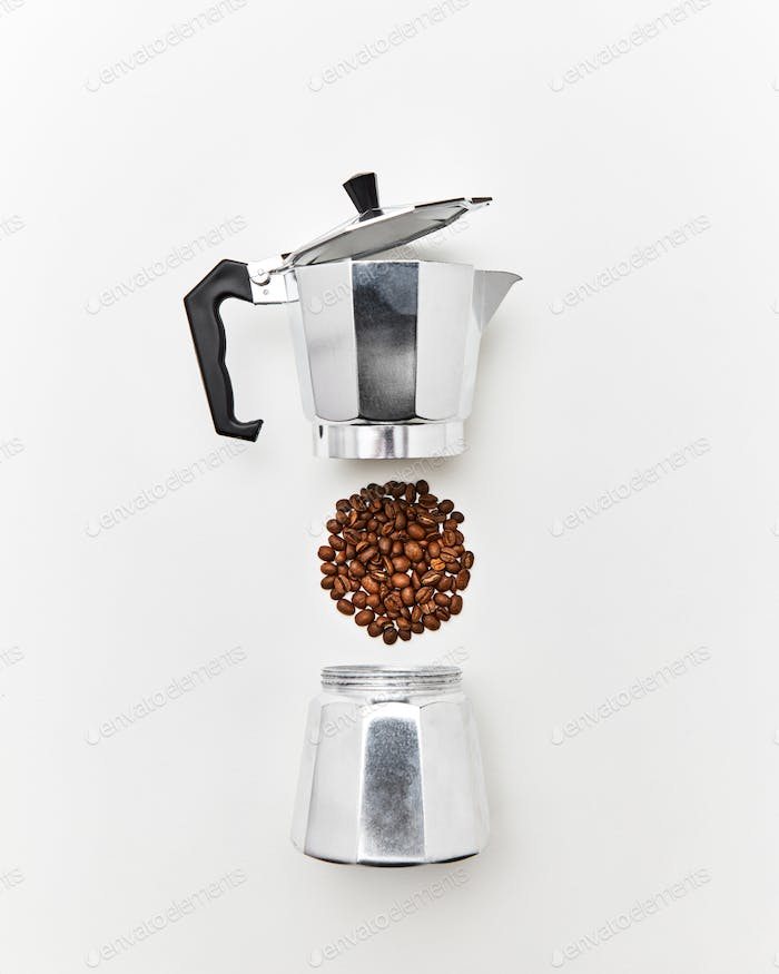 Metal coffee maker and a pattern of coffee beans in the shape of a circle on a gray background with